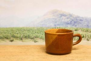 Brown coffee mug in front of field