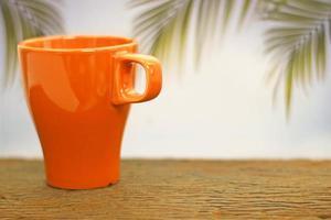 taza de café naranja sobre madera foto