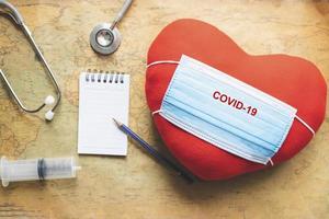 máscara covid-19 y corazón rojo foto