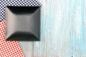 Black plate on wood table photo