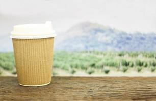 Coffee cup in front of field