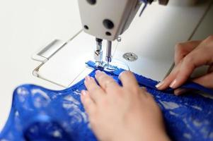Person sewing blue fabric photo