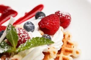 Berries with whipped cream on waffles