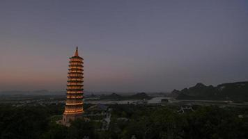 Illuminated Bai Dinh Pagoda tower at dusk