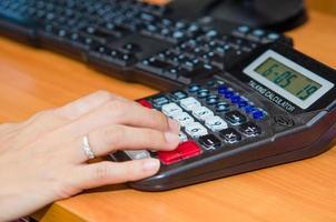 Hand typing on calculator