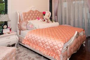 Bed with pink comforter and lots of pillows