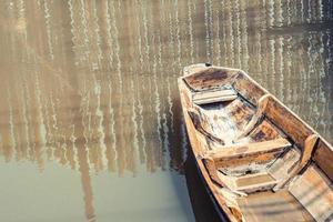 Viejo barco de madera solitario en el lago foto