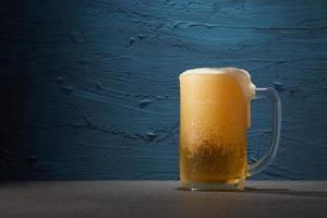 Cerveza en una jarra sobre un fondo azul.