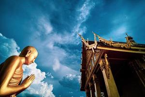 Thai Temple and golden monk statue photo
