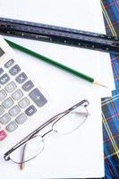 Calculator, glasses, pencil and protractor scale. photo