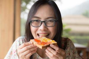 mujer tailandesa comiendo pan con mermelada