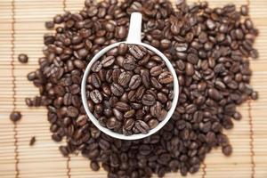 granos de cafe en una taza de cafe