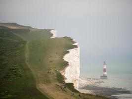Lighthouse next to cliff with groups of people walking