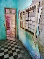 Room with checkered floor and worn down colorful walls photo