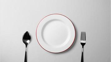 Plate, spoon, and fork on white table photo