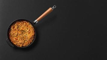 Noodles in pan on black background