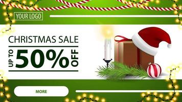 Christmas sale, up to 50 off, green horizontal modern web banner with button, garland, gift with Santa Claus hat, candles, Christmas tree branch and Christmas ball