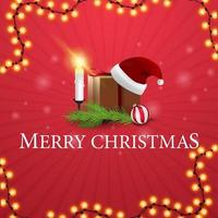 Merry Christmas, square red postcard with gift with Santa Claus hat, candles, Christmas tree branch and Christmas ball