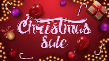 Red Christmas sale banner with garland, Christmas balls, gift, candy cane and balloons. Top view. vector