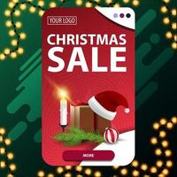 Christmas sale, vertical red discount banner with button, gift with Santa Claus hat, candles, Christmas tree branch and Christmas ball