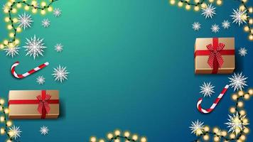 Gifts, candy canes, paper snowflakes and garland on blue table, top view. Background for discount banner or greeting postcard