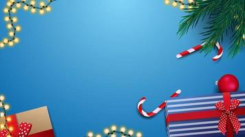 Gifts, candy canes, Christmas tree branch and garland on blue table, top view. Background for discount banner or greeting postcard