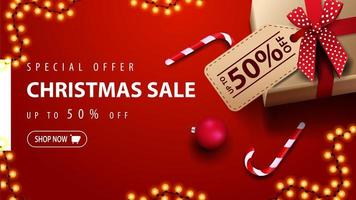 Special offer, Christmas sale, up to 50 off, red discount banner with gift box, Christmas balls and candy cane, top view
