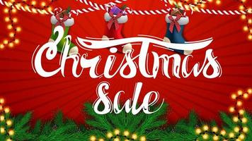 Christmas sale, beautiful red discount banner with Christmas tree branches, garlands and Christmas stockings