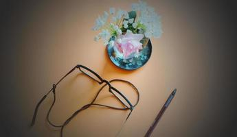 Black eyeglasses and next to blue and white flowers on ceramic plate