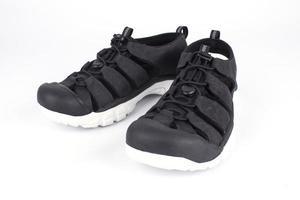 Par de zapatillas negras sobre fondo blanco.
