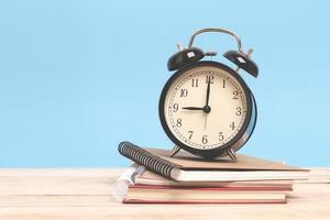 Clock on books on wooden desk photo