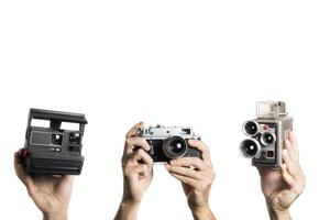 Vintage film and video cameras held by hands on white background