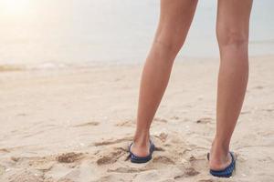 Mujer joven con sandalias flip flop en la playa