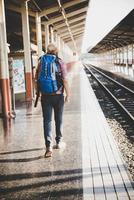 Young hipster man waiting on the station platform with backpack