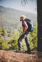 Hiker with big traveling backpack traveling to the mountain
