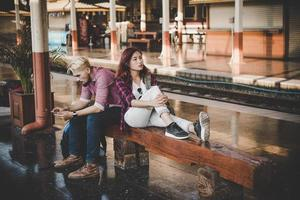 Young hipster couple sitting on wooden bench at train station