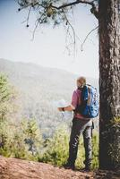 Hiker with map and big backpack traveling to the mountain