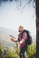 Hiker with map and big traveling traveling to the mountain