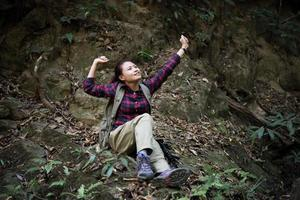 Woman hiker in forest taking a rest