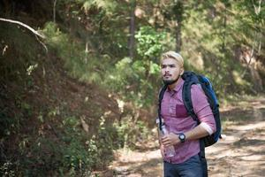 Happy hipster man tourist hiking in nature forest