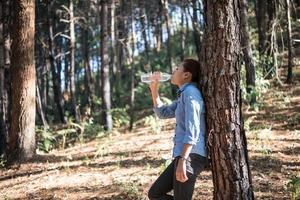 Portrait of female backpacker drinking fresh water in a pine forest