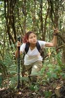 Caminante joven activo caminando por el bosque foto