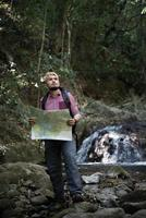 Adventure man observing map on a mountain path photo