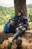 Portrait of a young man sitting alone by a tree with backpack photo