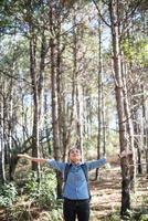 Young hipster woman enjoying nature with outstretched arms photo