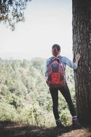 Hiker with backpack on top of a mountain photo