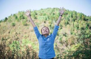 Young woman standing looking to the sky with raised hands
