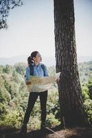 Young woman backpacker hiker reading map hiking trip. Relaxing on holiday. photo