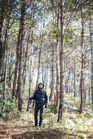 Joven con una mochila relajarse al aire libre en un bosque de pinos foto