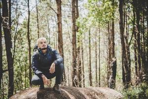 hombre en la cima de la montaña sentado en la roca foto
